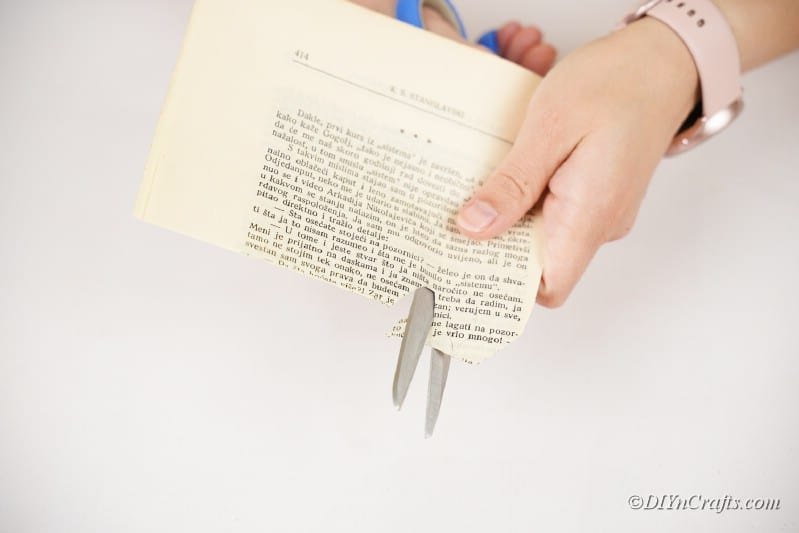 cutting book page with scissors