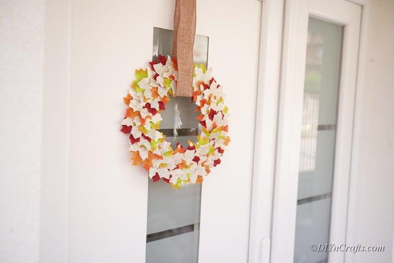 Herbstkranz an der Tür hängen