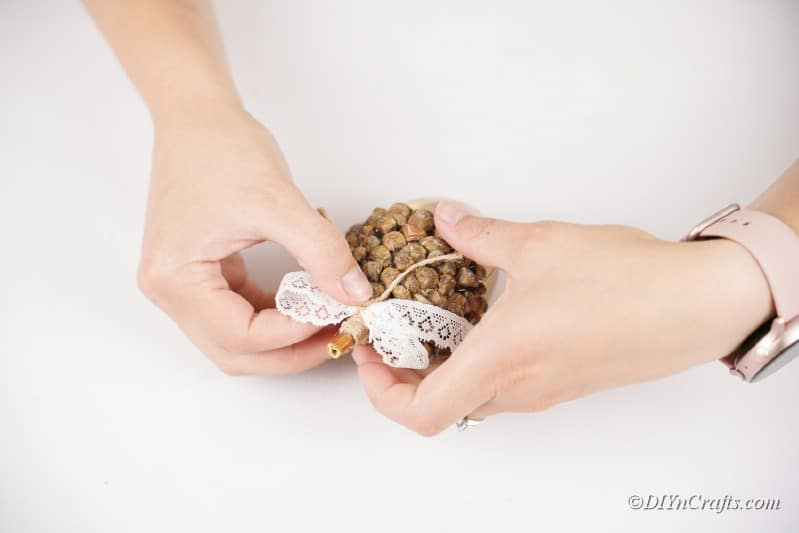 placing ribbon on a gold acorn shaped craft on white table