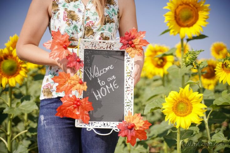 woman holding fall themed sign in sunflower field