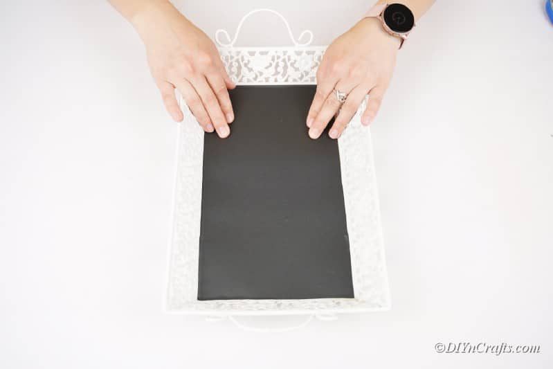 applying adhesive chalkboard sheet to tray