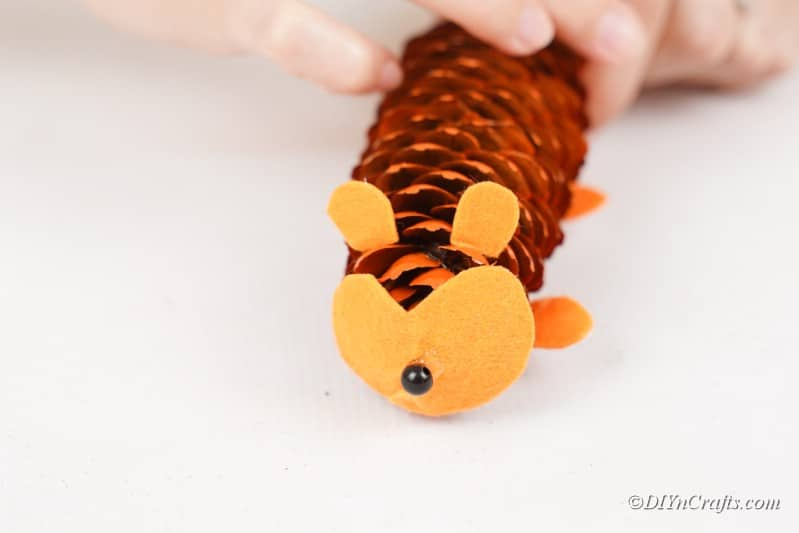 gluing decorations on to a pinecone