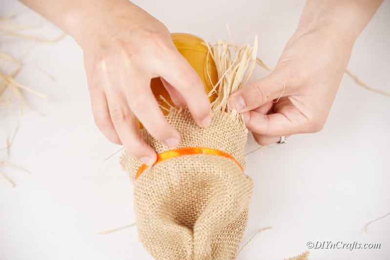 inserting straw into scarecrow craft