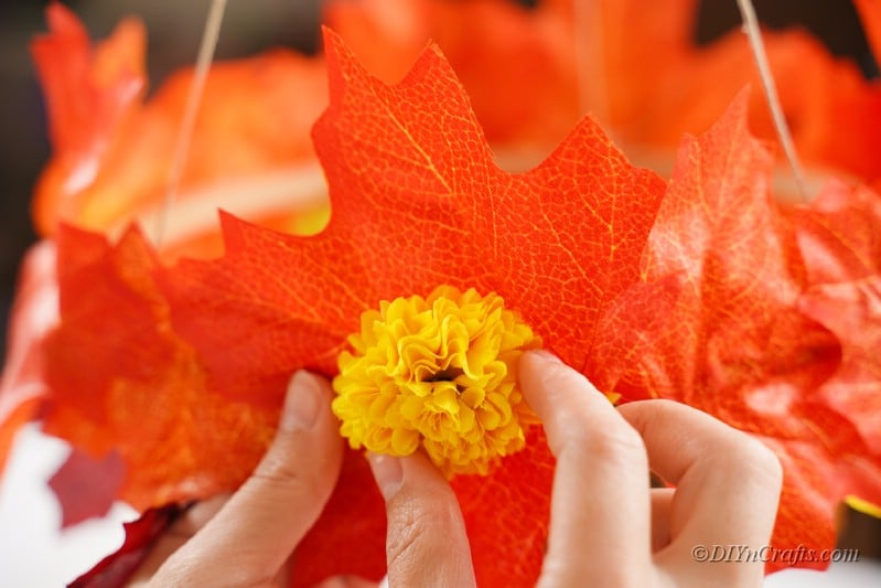 hand adding flowers to fake leaves craft