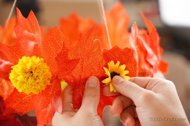 Hand pressing fake sunflower into oraneg leaf