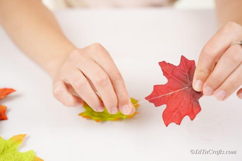 stringing fake leaves onto thread