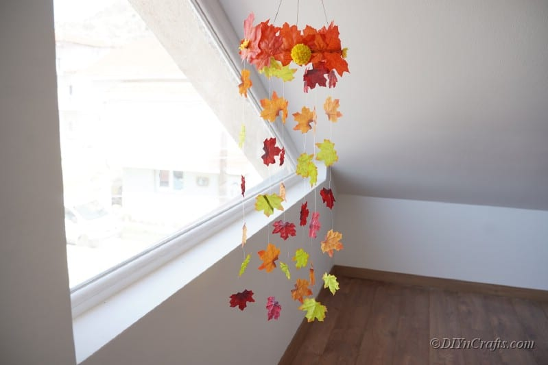 Mobile made of artificial leaves hanging by large window against white wall