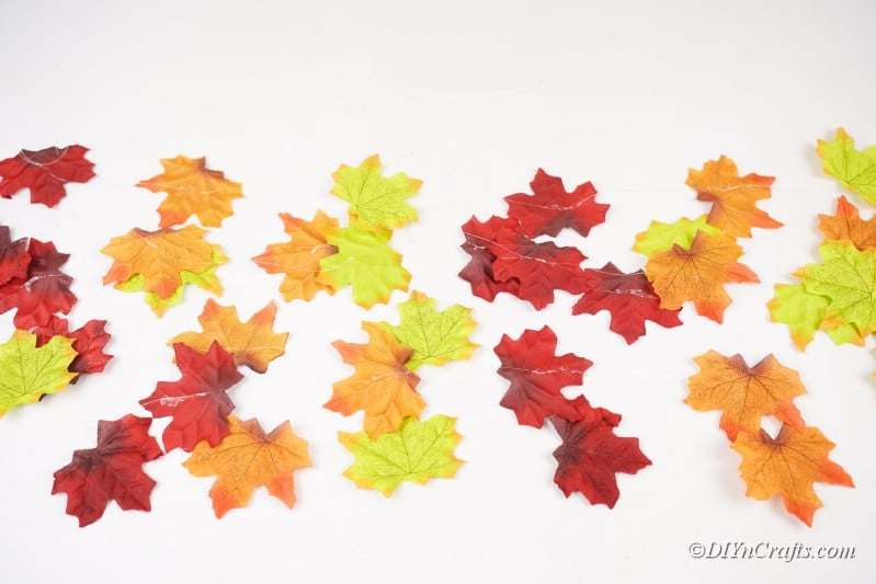 Strings of fake leaves laying on white table