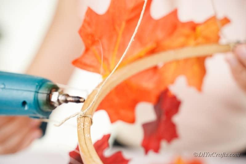 hot glue gun on craft hoop with leaves