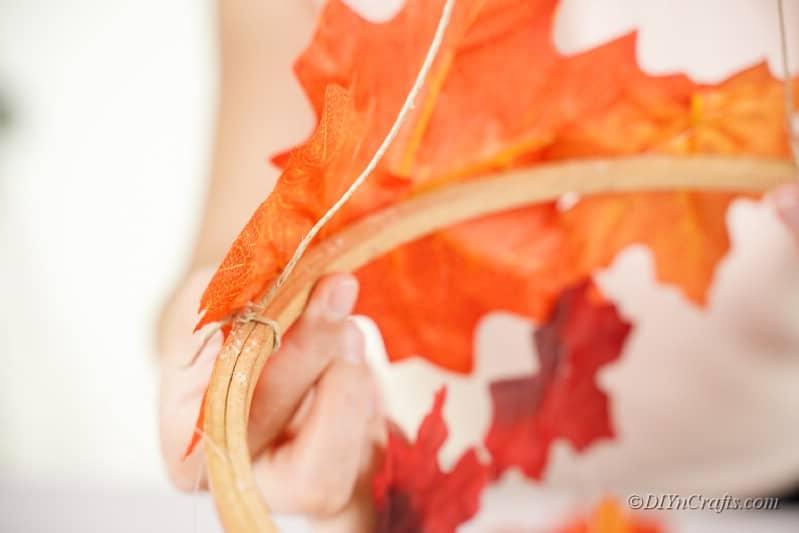 Twine glued onto embroidery hoop next to orange leaf