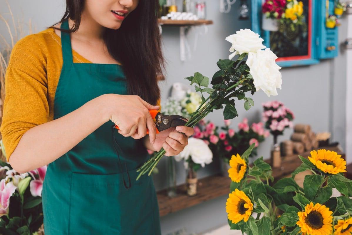 Florist preparing cut flowers.