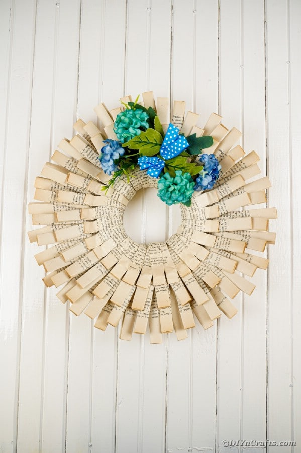 Old book page wreath on white wall