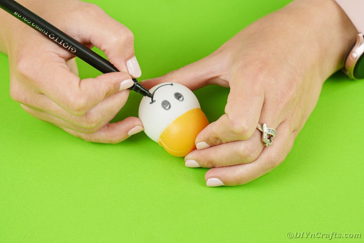 Drawing face on ping pong ball ornament