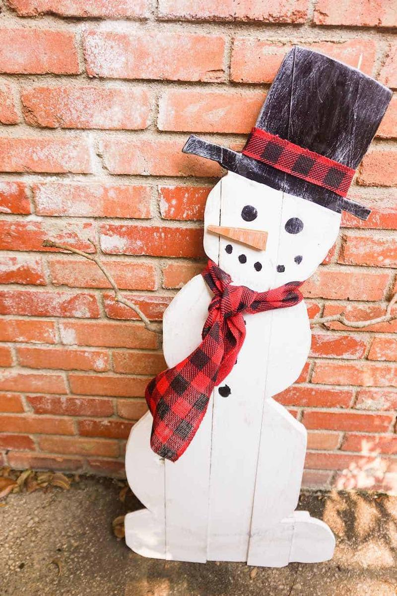 Wooden snowman by brick