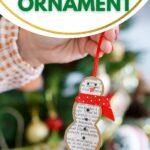 Woman holding paper snowman ornament