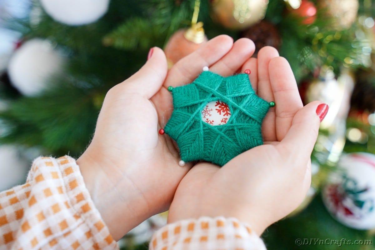 Woman holding yarn star ornament