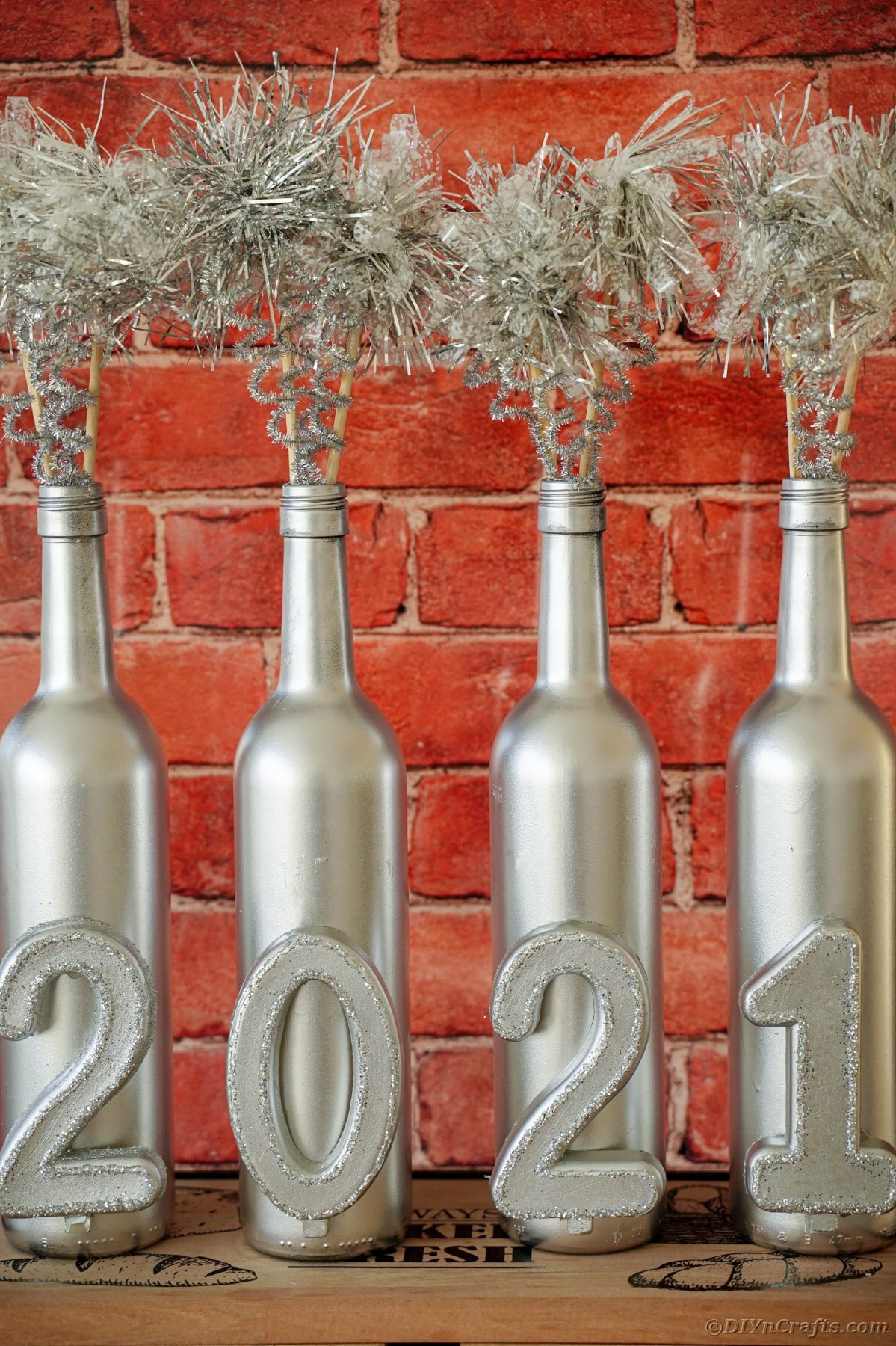Silver wine bottles by red brick