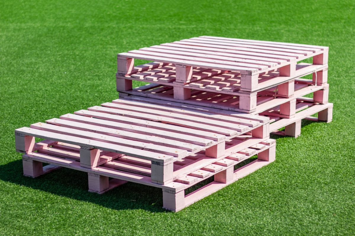 pink painted pallet in the green grass