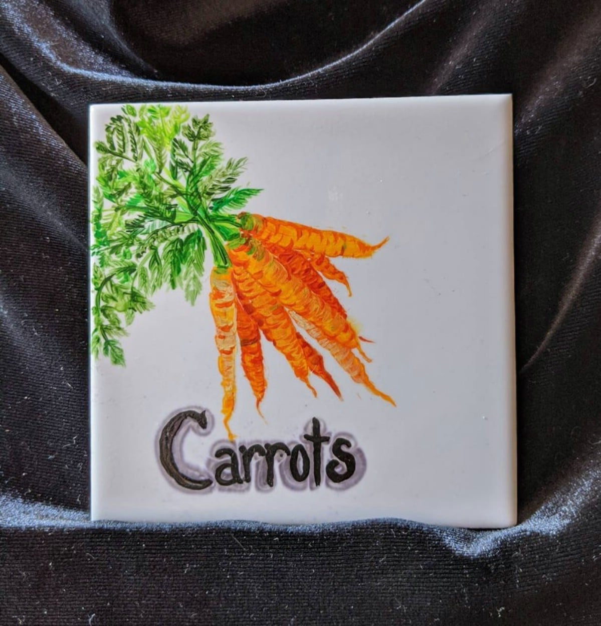 White tile with carrots painted and word carrots painted on top