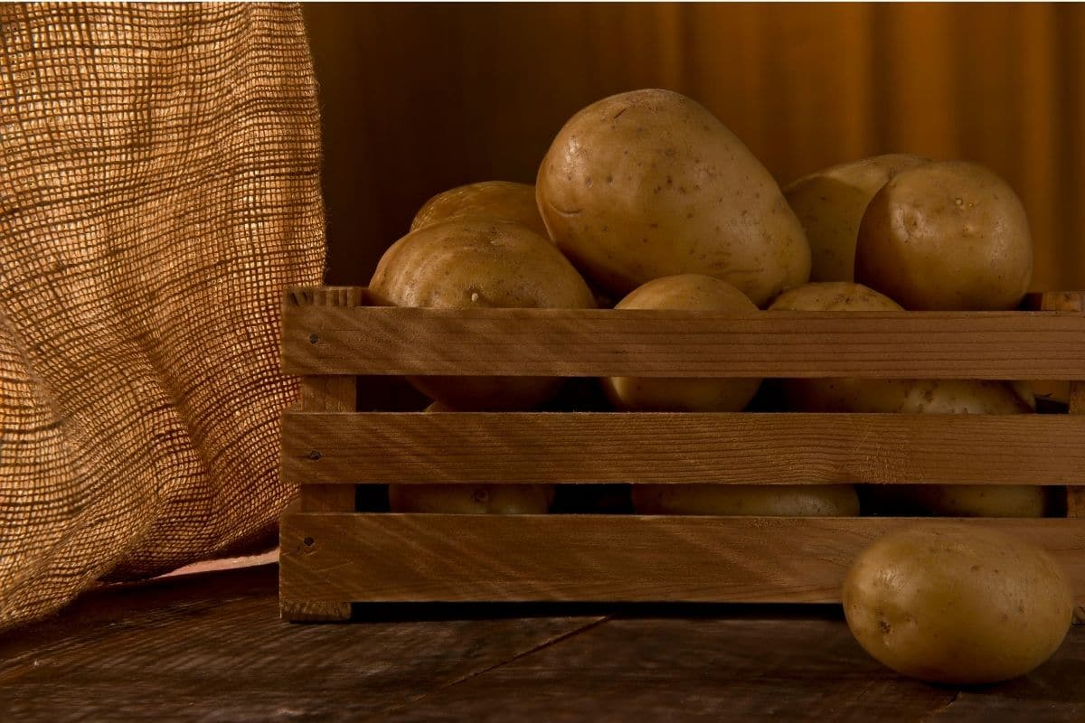 potatoes in a wooden box stored in a dark place