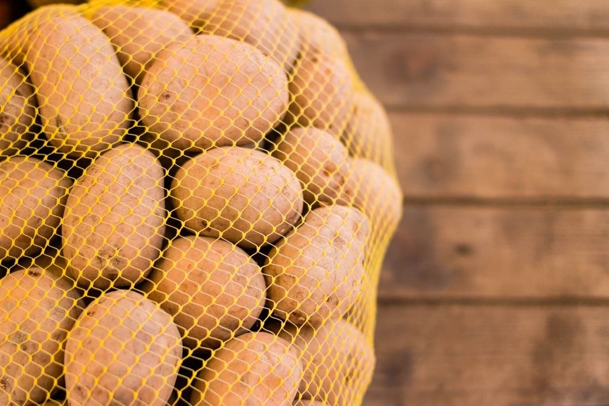 potatoes stored in a netted bag to encourage net flow and not trap moisture inside to prevent getting bad quickly lying in the wooden table