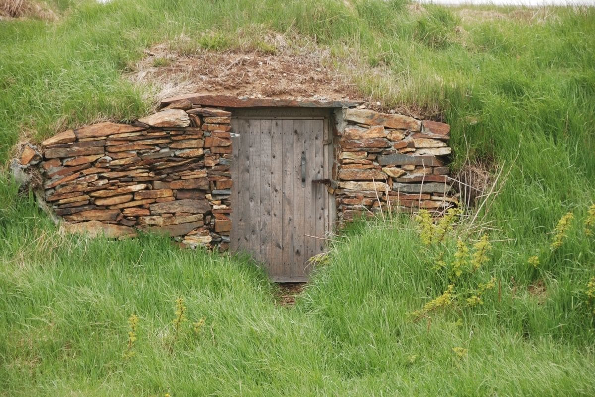 a root cellar under the hill to provide cold and dark environment to store potatoes to prolong its good quality