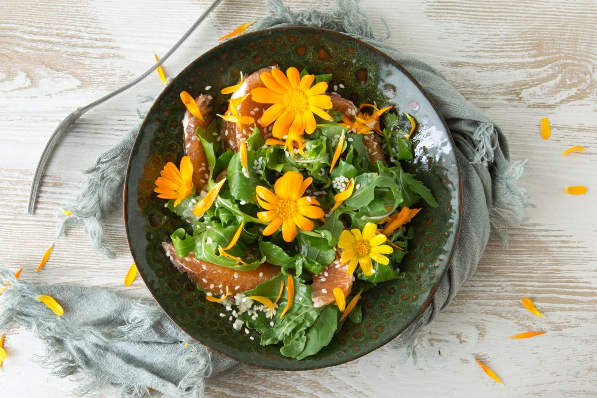vegetarian flat lay of food with arugula, orange, sesame seeds and edible marigold flowers in the table