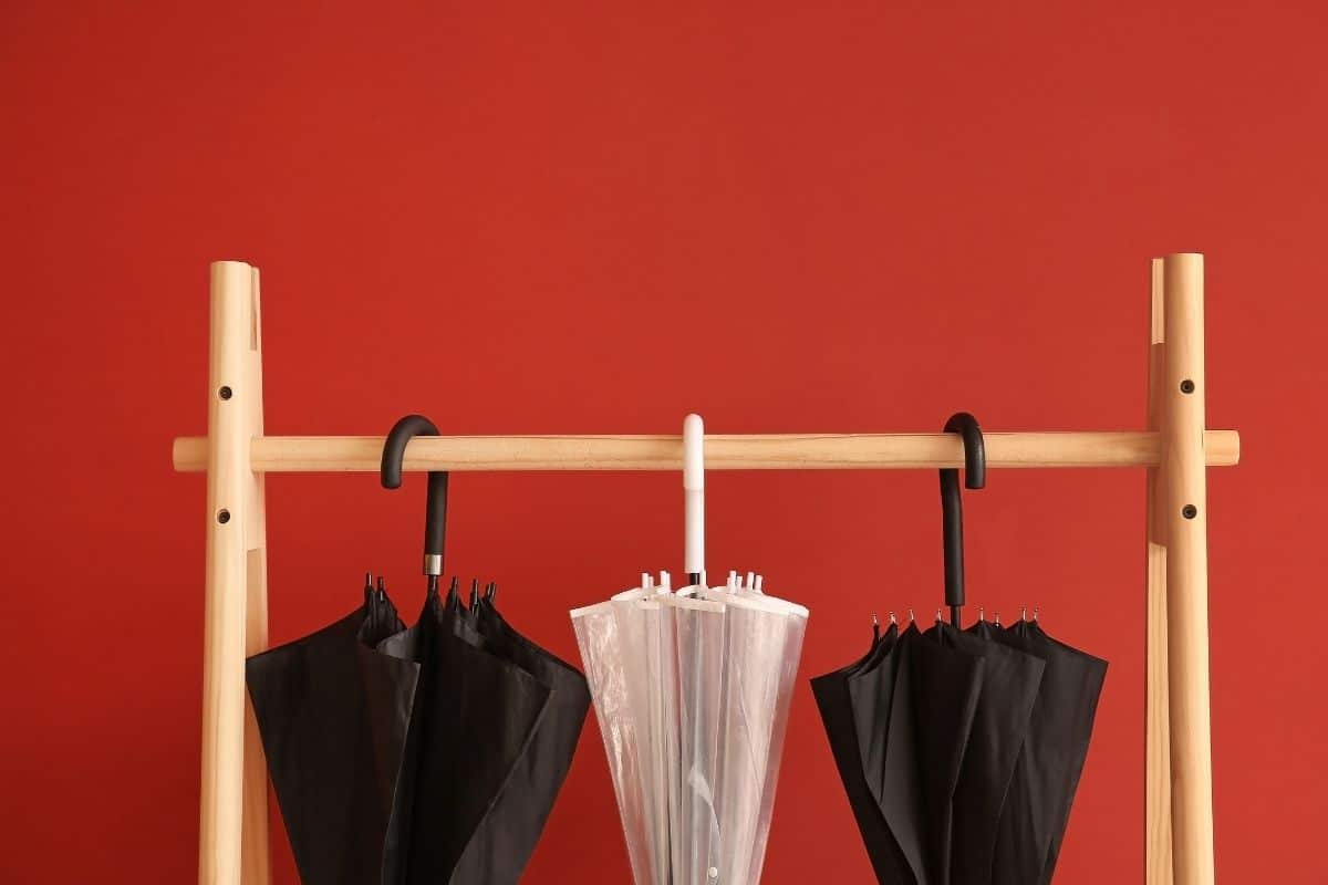 umbrella rack against a red wall
