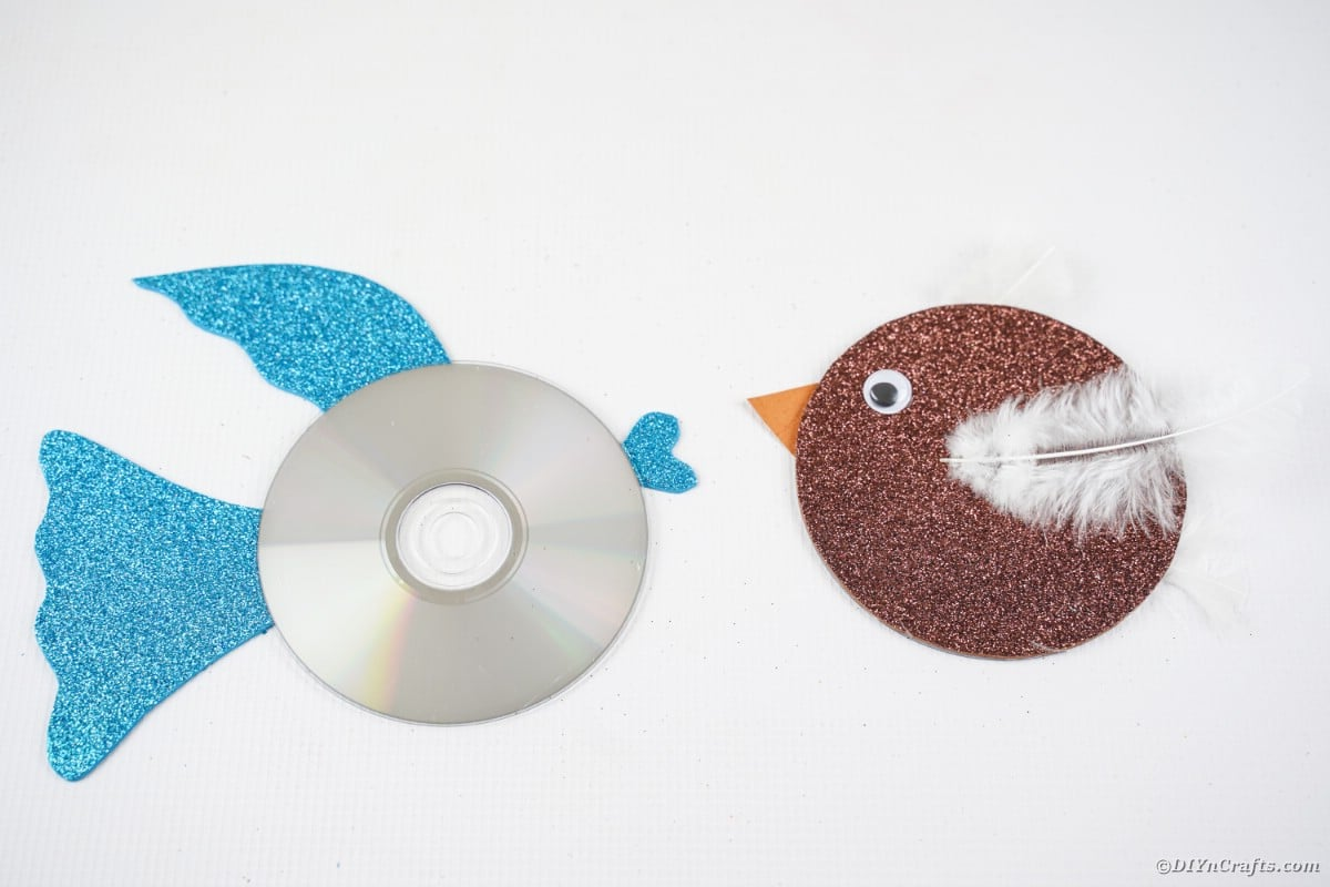 CD bird and CD fish on white table