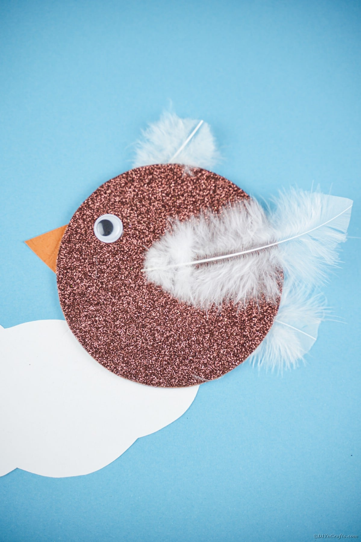 Brown CD bird on blue paper with clouds