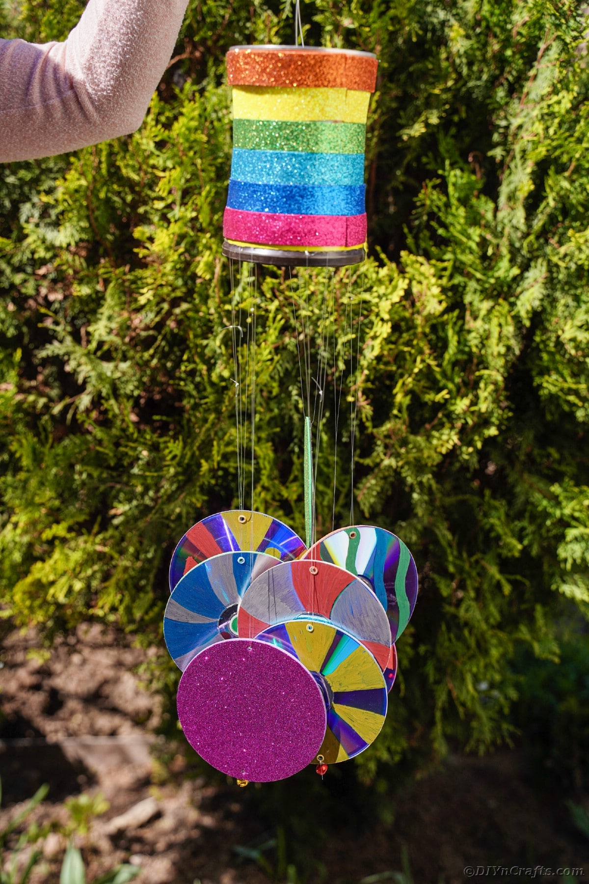 Woman holding colorful wind chime by bush