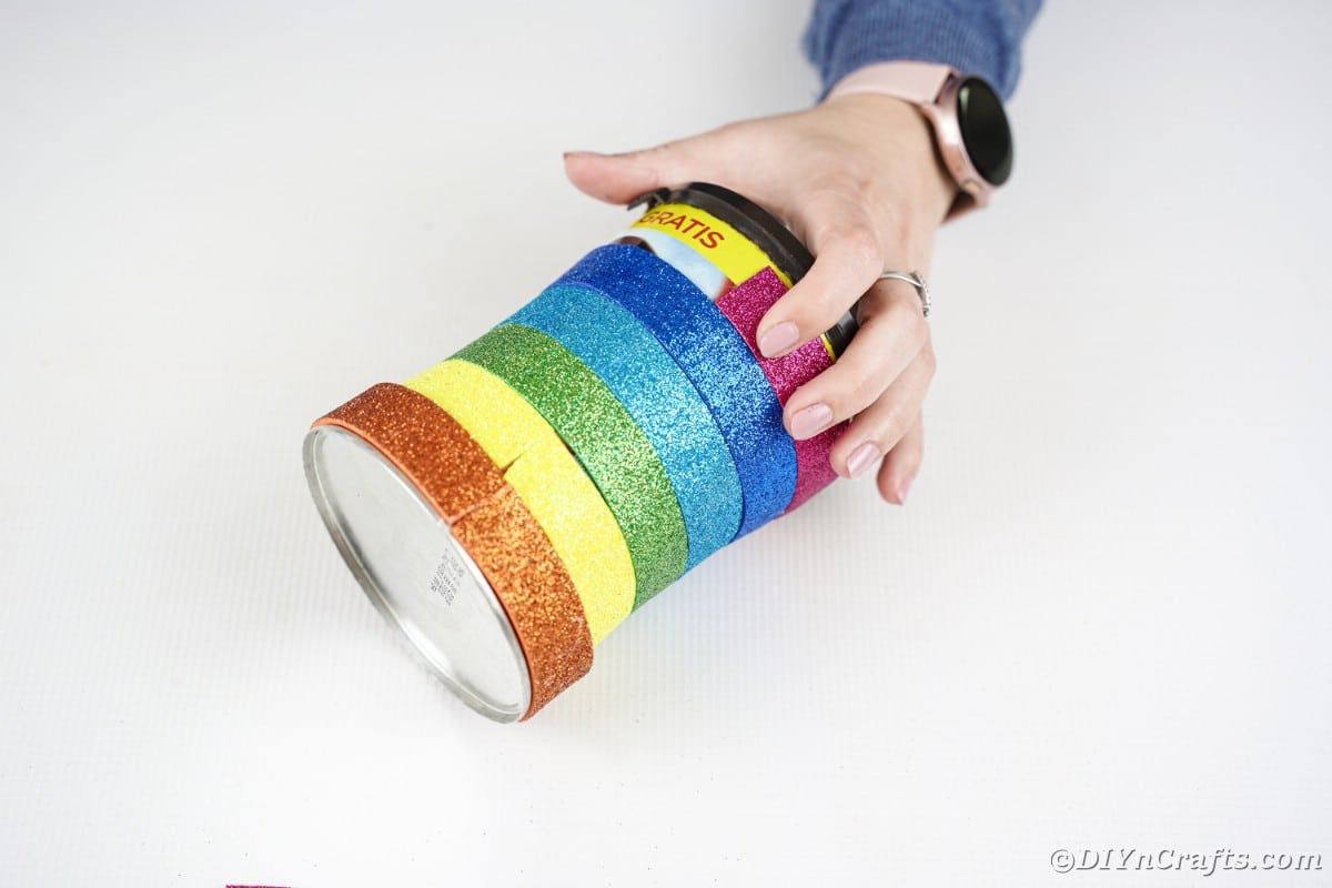 Woman gluing paper strips to can