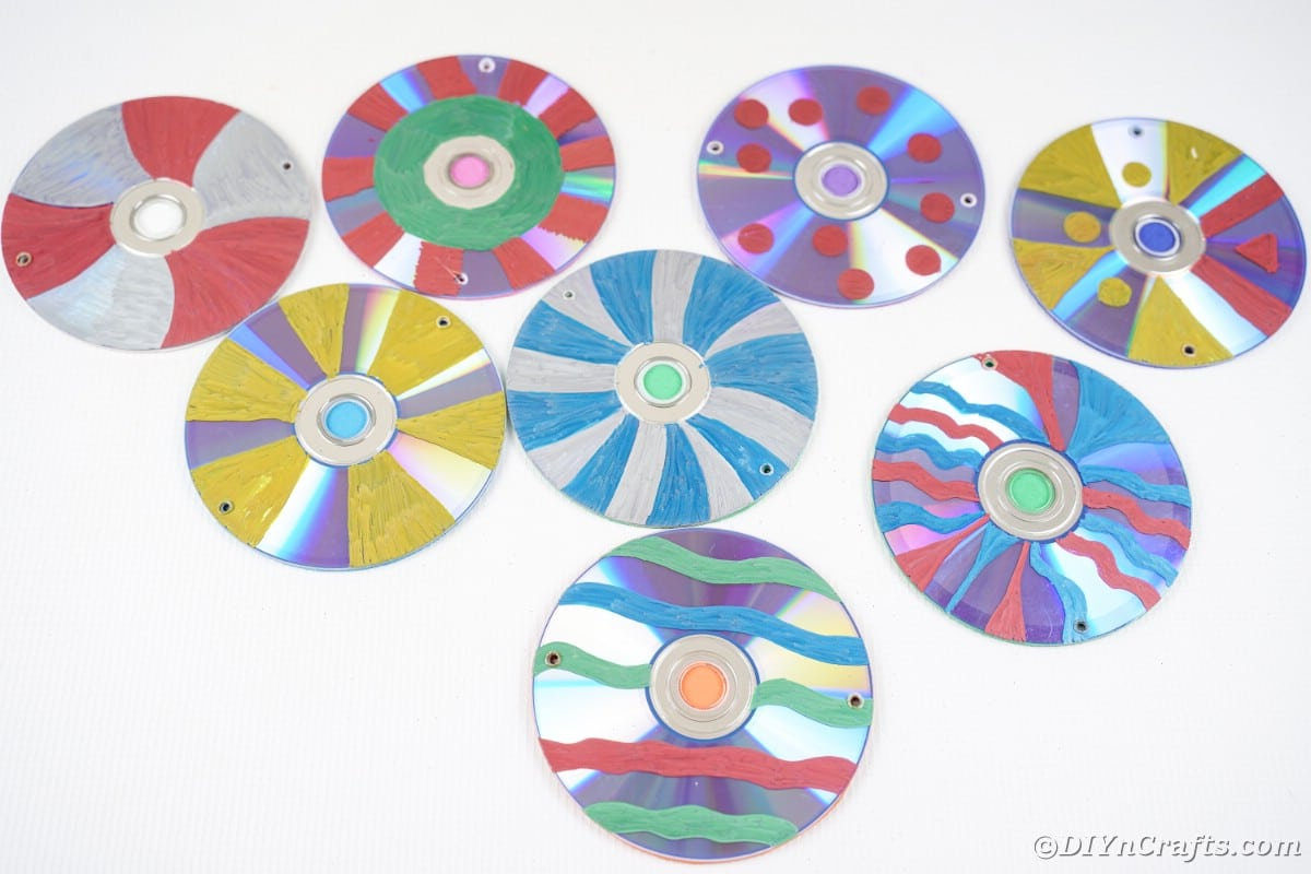 Colorful painted CDs on white table