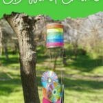 Wind chime outside with green overly and white text that says DIY wind chime
