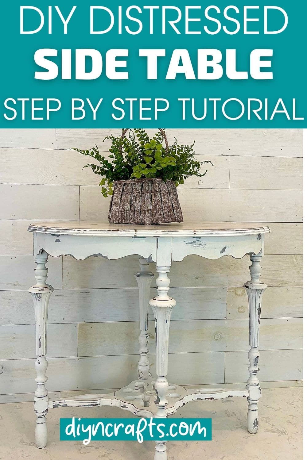 Basket of greenery on top of distressed white side table