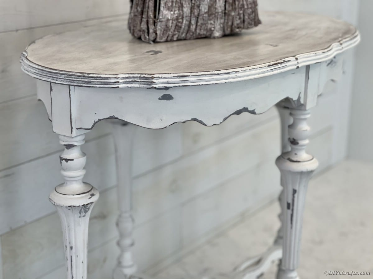 Front of distressed side table against white wall