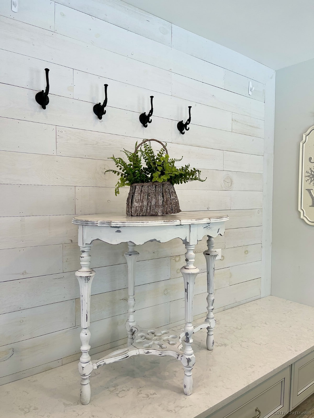 Distressed side table on white table against shiplap wall