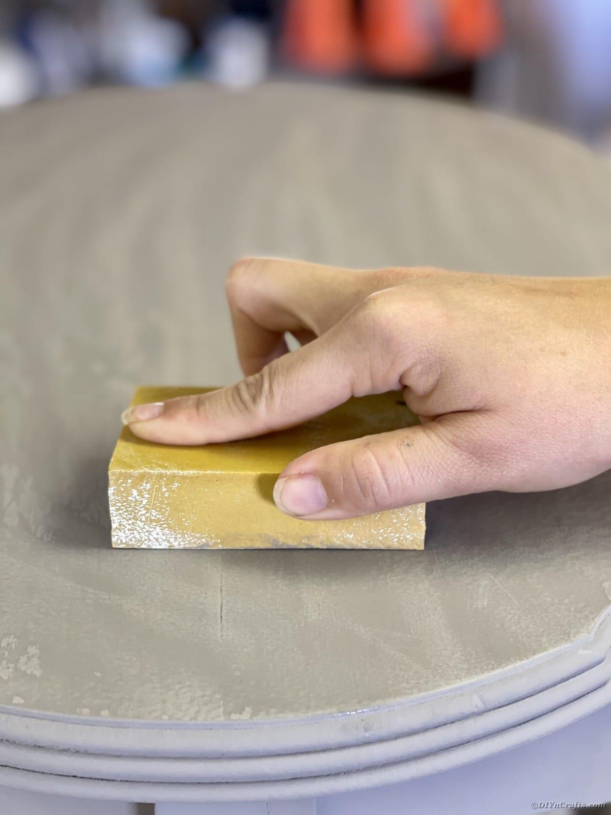 Hand holding sanding block on grey table
