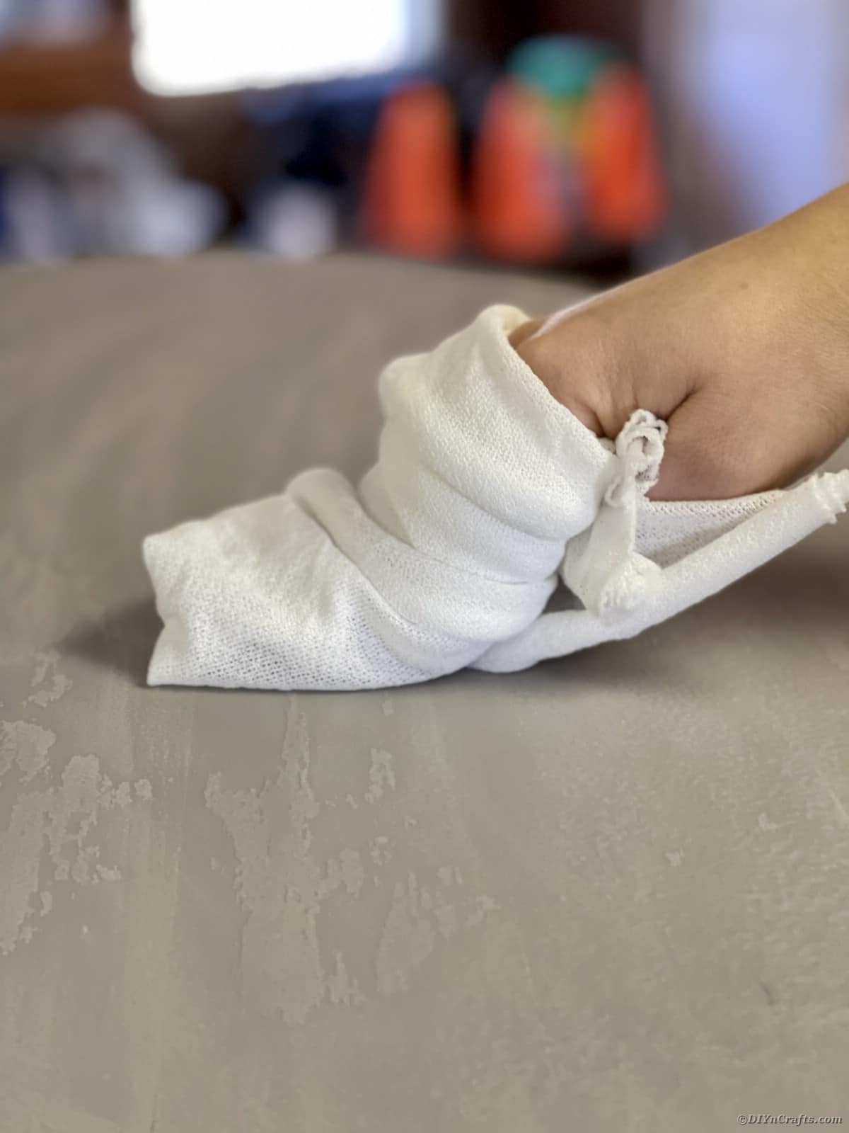 Hand with white cloth wiping top of table