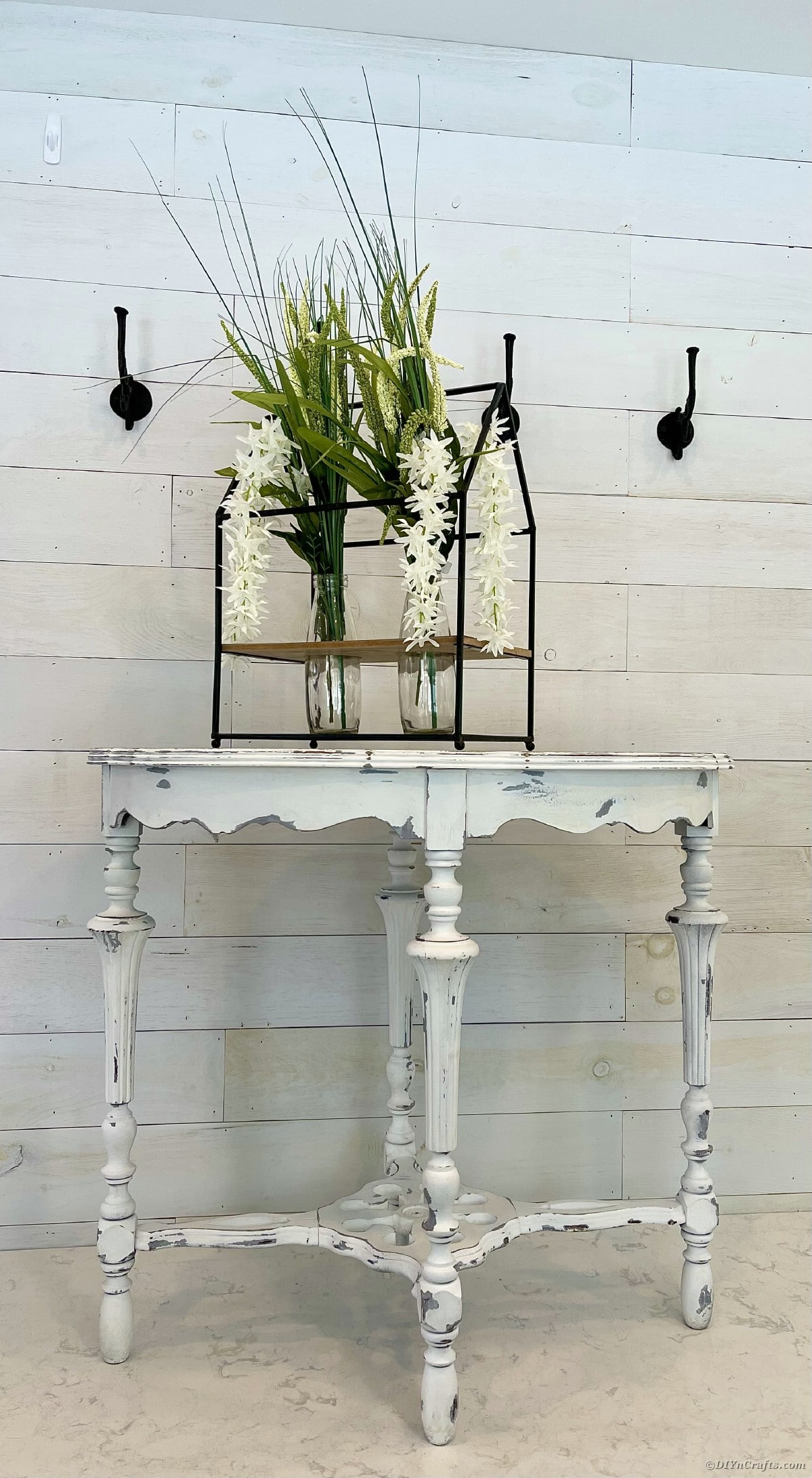 Weathered white side table with floral display against white wall