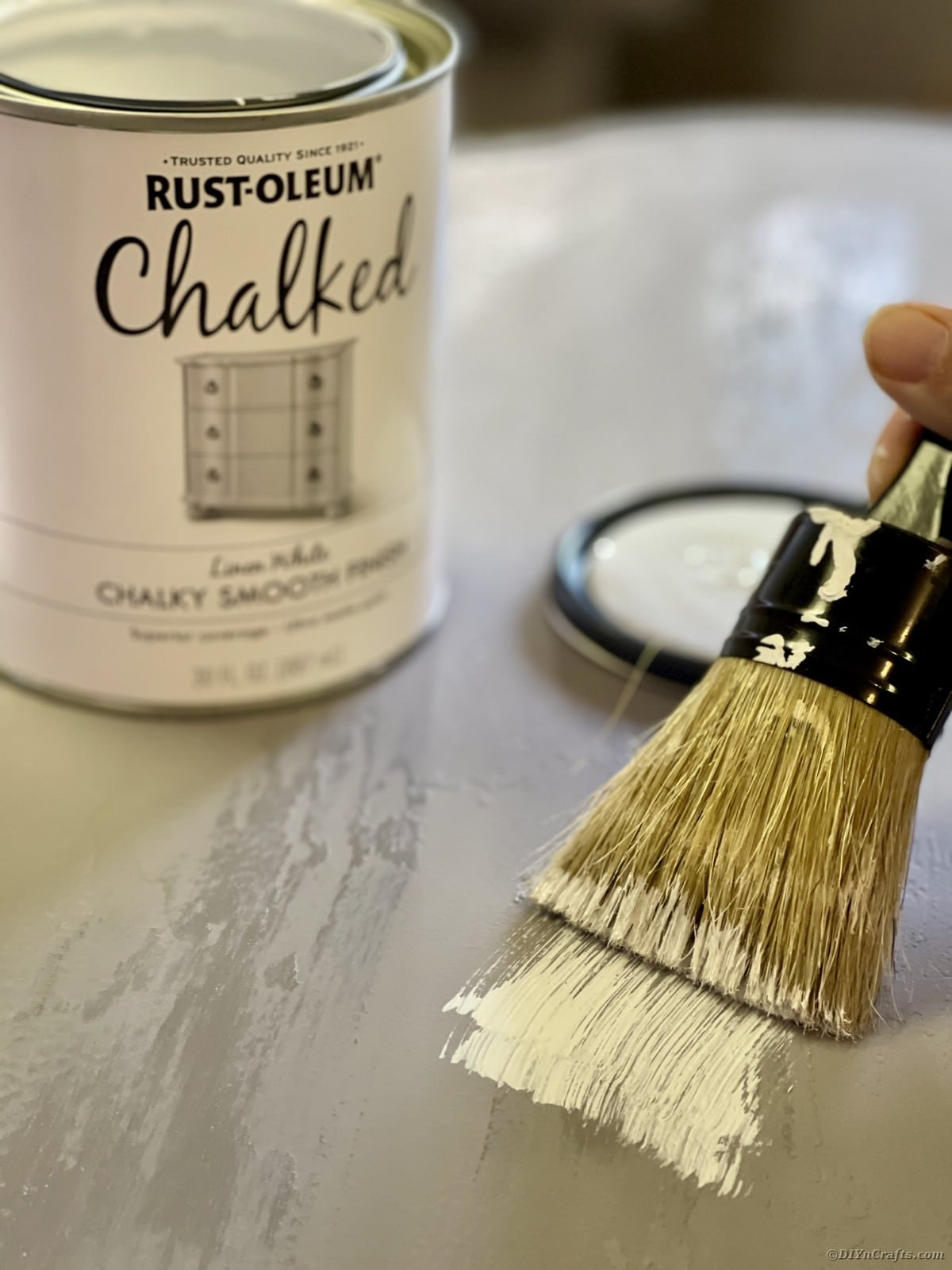 Paintbrush with white paint going over top of grey table