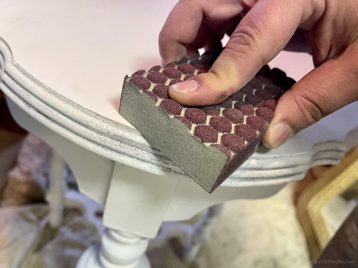 Hand holding sanding block on corner of white side table