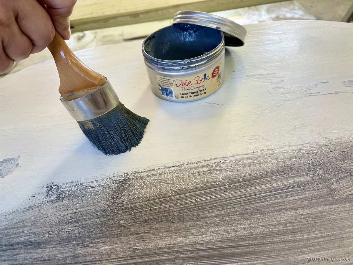 Dark paint brush wiping wax onto top of table