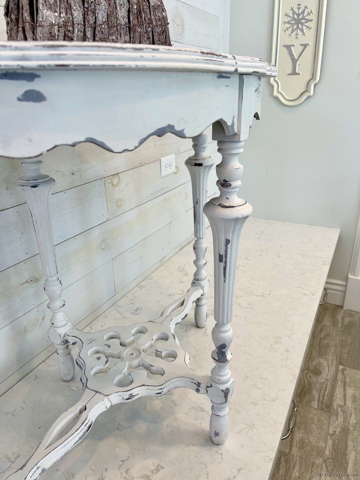 Finished distressed side table on white table with white brick wall