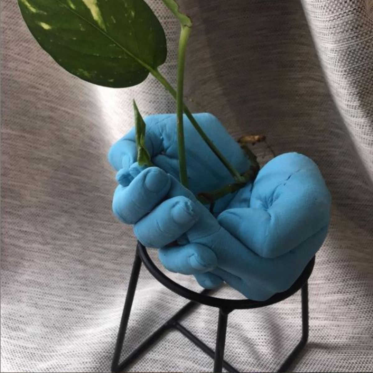 painted blue hand planter, hand shaped pot. with a plant