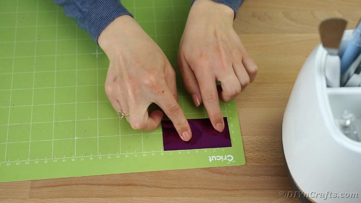 Placing purple vinyl on green cricut mat