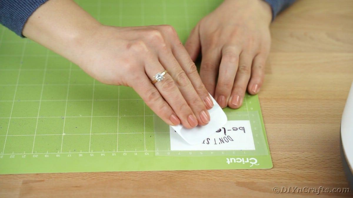 Rubbing transfer tape onto vinyl message