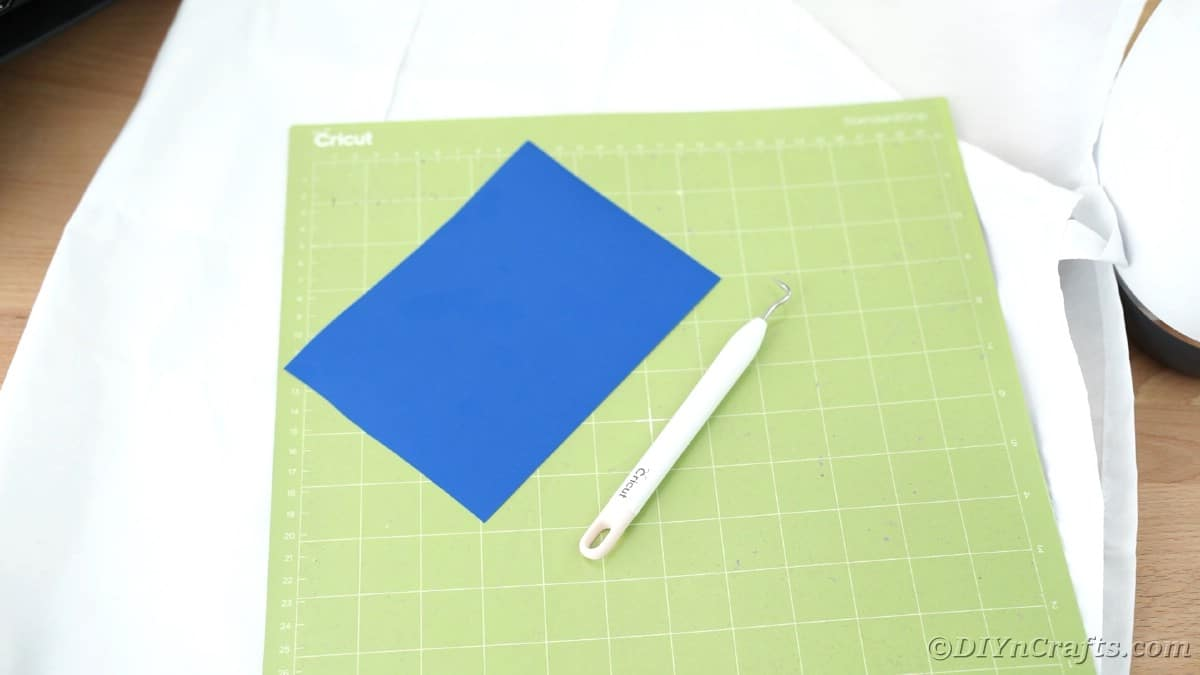 Blue vinyl and weeding tool on Cricut mat
