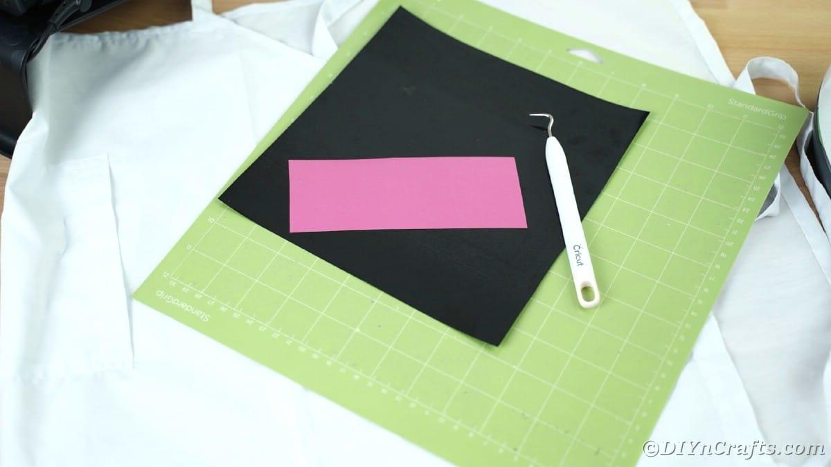 Black and pink vinyl on green Cricut mat