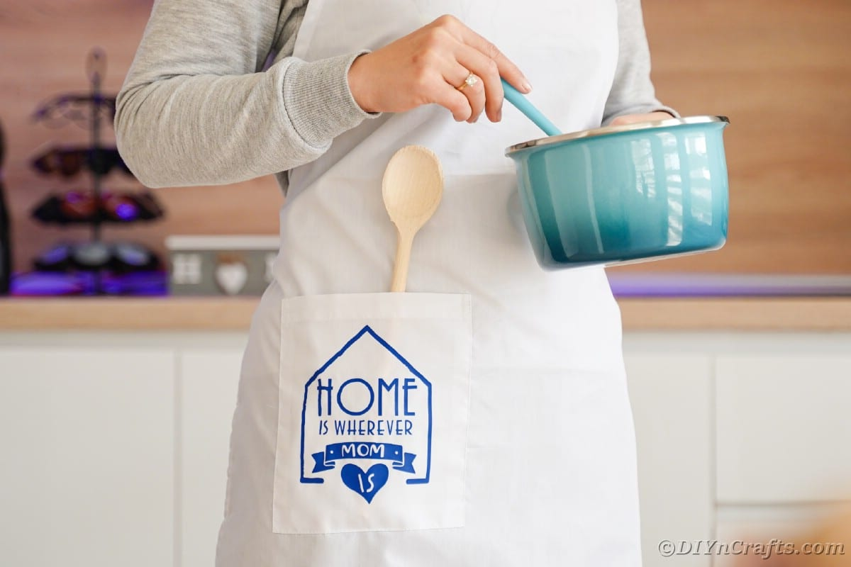 Woman in white apron with blue messag eon pocket